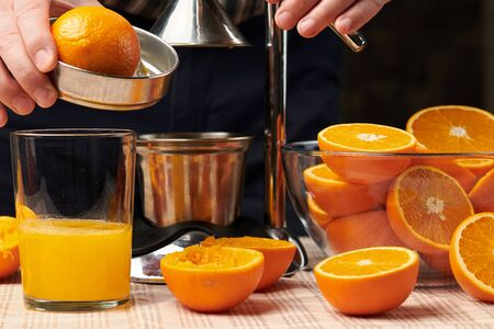 Squeezing an orange with a manual press, close view, making a glass of fresh. Fresh oranges on a wooden table, whole, squeezed and sliced. Stok Fotoğraf