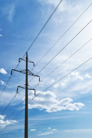 high-voltage electric line against a bright beautiful sky