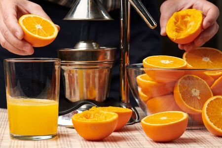 Squeezing an orange with a manual press, close view, making a glass of fresh. Fresh oranges on a wooden table, whole, squeezed and sliced. Imagens