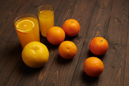 Fresh orange fruits whole and sliced on a dark wooden background - natural and healthy food. Glass of fruit cocktail.