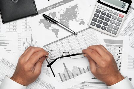 Top view of businessman working with financial statements. Modern black office desk with notebook, pencil and a lot of things. Flat lay table layout.