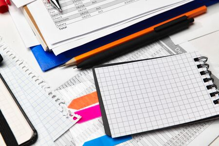 Top view of office worker's desk - work with financial reports, analysis and accounting, tables and graphs, various office items for bookkeeping
