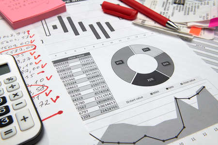business office desk closeup - financial reports, analysis and accounting, set of documents, tables and graphs, various items for bookkeeping, calculator