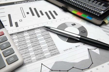 business office desk closeup - financial reports, analysis and accounting, set of documents, tables and graphs, various items for bookkeeping, calculator Archivio Fotografico