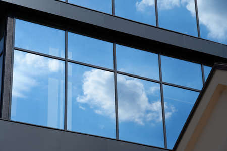 facade of a modern building on a bright Sunny day, blue sky and clouds reflecting in a glass, beautiful exterior of the new building Archivio Fotografico