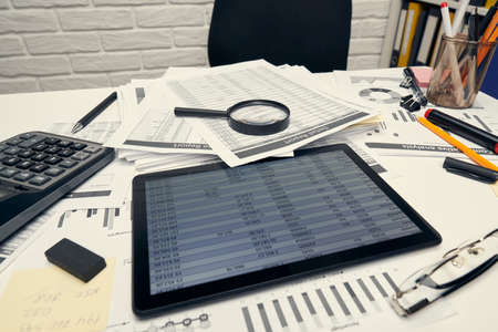Business analysis and accounting concept - Office desk closeup with document, spreadsheet, calculator, tablet pc. Foto de archivo