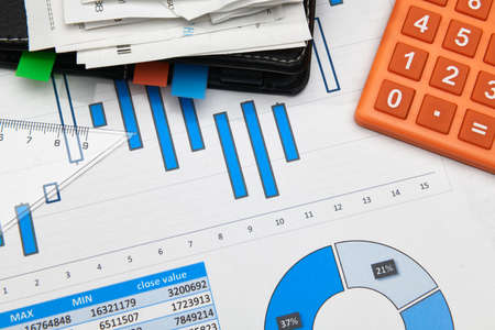 business office desk closeup - financial reports, analysis and accounting, set of documents, tables and graphs, various items for bookkeeping, calculator Reklamní fotografie