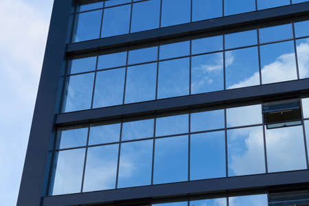 facade of a modern building on a bright Sunny day, blue sky and clouds reflecting in a glass, beautiful exterior of the new building Imagens