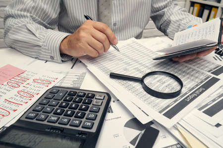 Business analysis and accounting concept - businessman working with document, spreadsheet, using calculator, tablet pc. Office desk closeup. Banco de Imagens