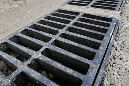 New rainwater grate on the road or sidewalk, installation in concrete. City sewage system for draining water during heavy rain Archivio Fotografico
