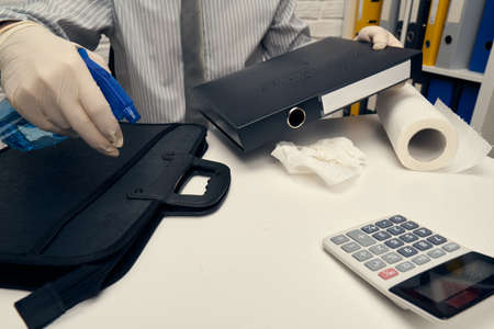 concept of cleaning or disinfecting the office desk - a businessman cleans the workplace, computer keyboard, document folders, uses a spray gun sanitizer, gloves and paper napkins. Banco de Imagens