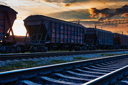 railway and rail cars in a beautiful sunset, dramatic sky and sunlight