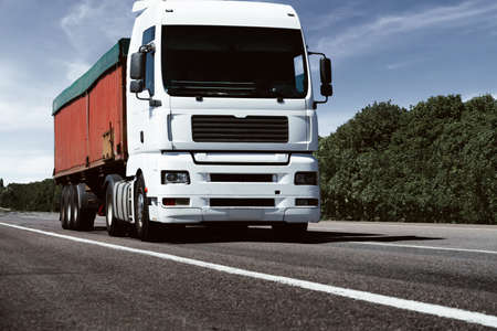 truck on the road, front view, empty space on a red container - concept of cargo transportation, trucking industry