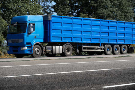 truck on the road, side view, empty space on a blue container - concept of cargo transportation, trucking industry
