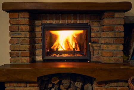 fireplace and fire close view as object or background, brick wall Standard-Bild