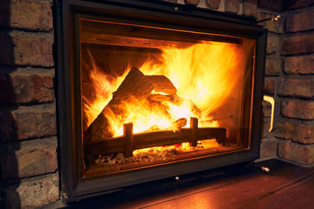 fireplace and fire close view as object or background, brick wall