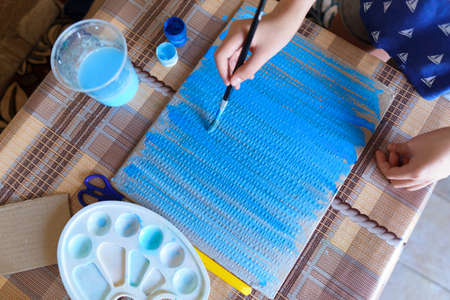 the girl draws blue gouache cardboard, makes a background, sits in the home kitchen