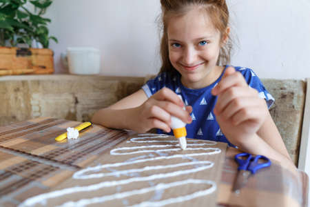 the girl makes crafts, glues cardboard, sits in the home kitchen