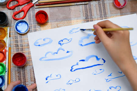 a girl drawing watercolor blue clouds on a blank white paper, artistic creation at home, makes creative artwork 写真素材