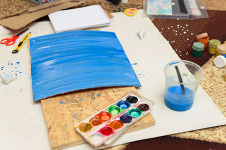 watercolor paints and paper closeup for drawing, artistic creation at home, workspace for make creative artwork