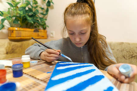 the girl draws blue gouache cardboard, makes a abstract background, sits in the home kitchen