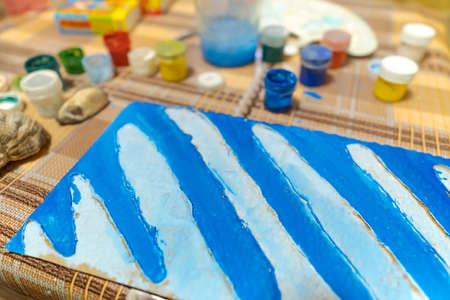 a table and workspace for creating a drawing on cardboard, artwork with blue gouache paint, abstract background 写真素材