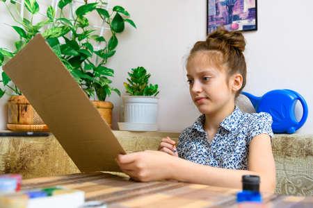 a girl drawing blue gouache cardboard, artistic creation at home, makes creative artwork