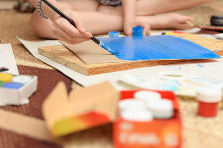 girl draws at home, artistic creation, makes creative artwork from paper, paints and brushes