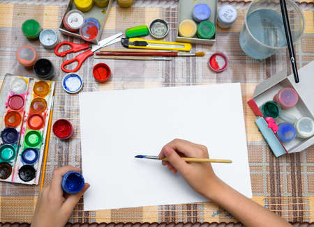 a girl drawing watercolor on a blank white paper, artistic creation at home, makes creative artwork 写真素材
