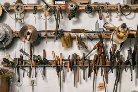 Variety of old vintage and modern household hand tools on a garage shelves in a DIY and renovations concept Standard-Bild