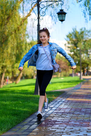 girl runs through sprinkled water in a city park, bright summer day 版權商用圖片