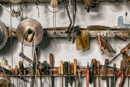 Variety of old vintage and modern household hand tools on a garage shelves in a DIY and renovations concept