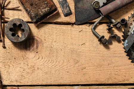 Old vintage household hand tools on a wooden background as frame and place for text