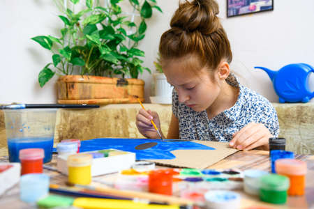 a girl drawing blue gouache cardboard, artistic creation at home, makes creative artwork