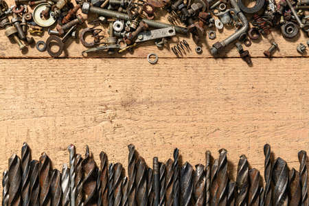 old vintage hand tools - set of drills, screws and nuts on a wooden background with blank space for text