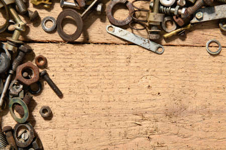 frame with blank space or place for text from old vintage hand tools, screws and nuts on a wooden background