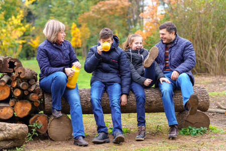 family relaxing outdoor in autumn city park, happy people together, parents and children, they drink tea, talking and smiling, beautiful nature