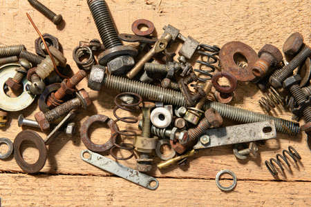 old vintage hand tools - set of screws and nuts on a wooden background
