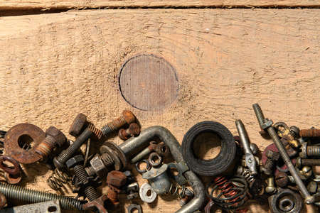 old vintage hand tools - set of screws and nuts on a wooden background with blank space for text