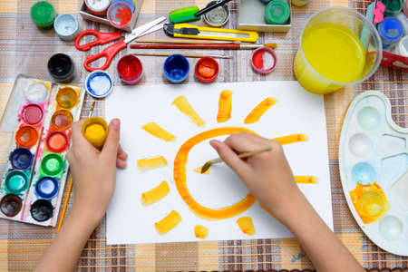 a girl drawing watercolor a big smiling sun on a blank white paper, artistic creation at home, makes creative artwork