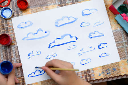 a girl drawing watercolor blue clouds on a blank white paper, artistic creation at home, makes creative artwork