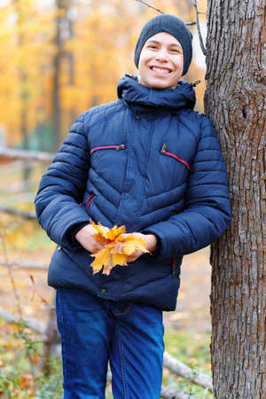 a boy running through the park and enjoys autumn, beautiful nature with yellow leaves