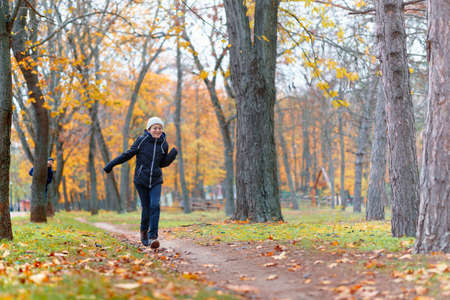teen girl and boy running through the park and enjoys autumn, beautiful nature with yellow leaves
