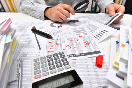 business concept - businessman working with reports in office, table and workspace close view, analyzing financial data, writes and counts