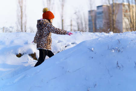 child girl runs and having fun in the winter forest near city, bright sunlight and shadows on the snow, beautiful nature.