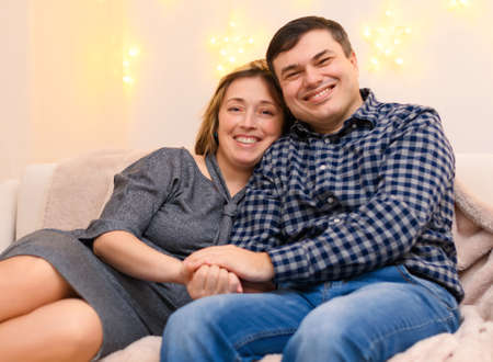 portrait of adult romantic couple sitting on a couch at home, holiday lights on a wall