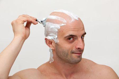 shaving blade: Young man shaving his head