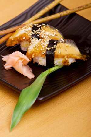 Plate of eel sushi with chopsticks Imagens