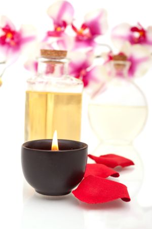 Body oils, rose petals and candle on white background