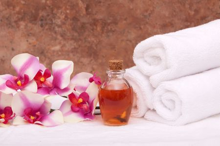 white towels: Aromatherapy oils, colorful orchid and white towels Stock Photo